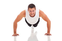 Fitness man push ups. Fitness man doing push ups over white background Royalty Free Stock Image