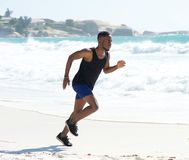 Fitness man running on the beach Stock Photography
