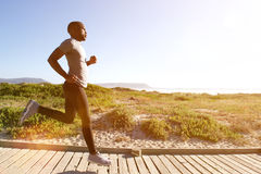 Fitness man running on the boardwalk at the beach Royalty Free Stock Photo