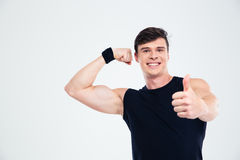 Fitness man showing his biceps and thumb up Stock Photo