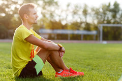 Fitness man sitting on grass and resting after sport exercises Stock Photography