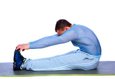 Fitness man sitting and making stretching exercises. Over white background Stock Photography