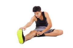 Fitness man sitting and making stretching exercises. Young fitness man sitting and making stretching exercises Stock Photos