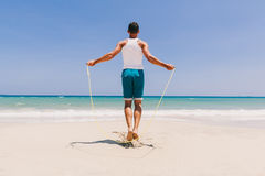 Fitness man skipping on the beach Royalty Free Stock Photos