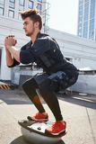 Fitness man in sports wear and EMS costume doing exerciss on the disk outdoors stock photo