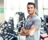 Fitness man standing with arms folded at gy Stock Photo