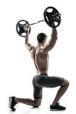 Fitness man standing on knee and holding barbell, rear view Royalty Free Stock Photography