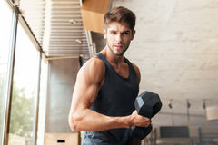Fitness man stands sideways in gym. Looking at the camera. with dumbbell stock photo