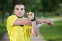 Fitness man stretching arm shoulder before outdoor workout. Sporty male athlete in an urban park warming up. Stock Images