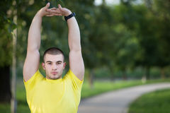 Fitness man stretching arm shoulder before outdoor workout. Sporty male athlete in an urban park warming up. Fitness man stretching arm shoulder before outdoor Stock Photos