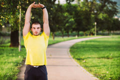Fitness man stretching arm shoulder before outdoor workout. Sporty male athlete in an urban park warming up. Fitness man stretching arm shoulder before outdoor Stock Images