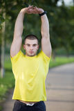 Fitness man stretching arm shoulder before outdoor workout. Sporty male athlete in an urban park warming up. Fitness man stretching arm shoulder before outdoor Stock Image