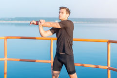 Fitness man stretching arms, shoulder. Runner warming up and exercising. Fitness man stretching arms, shoulder. Runner warming up and exercising Stock Images