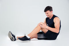 Fitness man suffering from pain in a knee Royalty Free Stock Photos