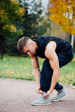 Fitness man tie shoelaces in the fall park. Stock Photos