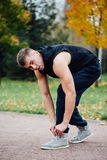 Fitness man tie shoelaces in the fall park. Stock Image