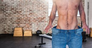 Fitness man Torso wearing a huge jeans in a gym to show how he lost weight. Digital composite of Fitness man Torso wearing a huge jeans in a gym to show how he Stock Image
