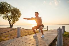 Fitness man training air squat exercise on beach outside. Fit male exercising crossfit outside. Young handsome caucasian. Male fitness model and instructor stock photo