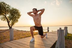 Fitness man training air squat exercise on beach outside. Fit male exercising crossfit outside. Young handsome caucasian. Male fitness model and instructor stock photography