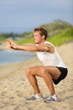 Fitness man training air squat exercise on beach. Outside. Fit male exercising crossfit outside. Young handsome caucasian male fitness model and instructor Royalty Free Stock Photo