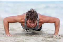 Fitness man training arms doing push ups exercise. Fit fitness man exercising arms muscles doing exercise push ups exercises. Caucasian male fitness athlete Stock Images