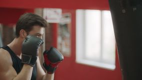 Fitness man training box kick in sport club. Boxer kicking boxing bag in gloves. stock footage