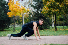 Fitness man training and jogging in fall park. Ready to start. Healthy lifestyle Royalty Free Stock Photo