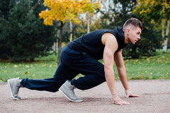Fitness man training and jogging in fall park. Ready to start. Healthy lifestyle Royalty Free Stock Images