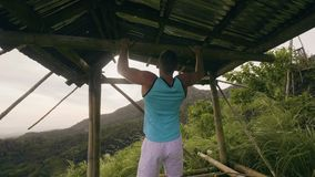 Fitness man training pulling up exercise on horizontal bar in tropical forest. Athlete man doing pull up workout on stock video footage
