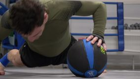Fitness man training push up exercise with med ball in gym. Close up athlete man pushing up on floor with fitness ball. Sport and healthy lifestyle stock video