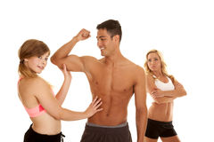 Fitness man with two women one mad arms folded Stock Photography