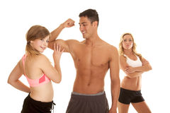 Fitness man with two women one touch muscle Stock Photography
