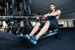 Fitness man using rowing machine at gym stock photo
