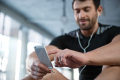 Fitness man using smartphone in gym. Portrait of a fitness man using smartphone in gym. Focus on smartphone Stock Image