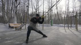 Fitness man using trx loop equipment for training on outdoor sport ground. Sport man exercising with trx fitness straps on winter training outdoor stock footage