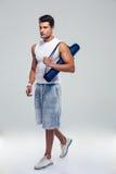 Fitness man walking with yoga mat Stock Photos