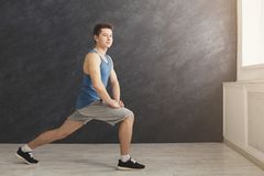 Fitness man warmup stretching training indoors. Fitness man warmup stretching training at gray background indoors. Young sporty guy makes aerobics exercise, copy Royalty Free Stock Images