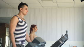Fitness man and woman walking on treadmill. In gym stock video