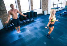 Fitness man and woman workout with jumping rope. Fitness men and women workout with jumping rope in crossfit gym Royalty Free Stock Photography