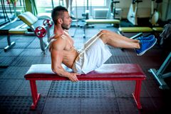 Fitness man working the abdomen at gym. Athletic fitness man working the abdomen at gym Royalty Free Stock Images