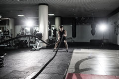 Fitness man working out with battle ropes at gym. Battle ropes fitness man at gym workout exercise fitted body. Fitness man traini. Ng with battle rope in Royalty Free Stock Images
