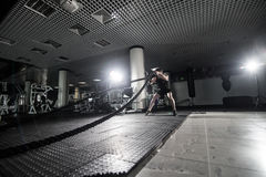 Fitness man working out with battle ropes at gym. Battle ropes fitness man at gym workout exercise fitted body. Fitness man traini. Ng with battle rope in Stock Photos