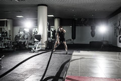 Fitness man working out with battle ropes at gym. Battle ropes fitness man at gym workout exercise fitted body. Fitness man traini. Ng with battle rope in Stock Images