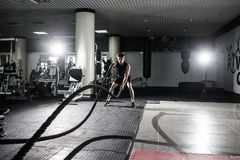 Fitness man working out with battle ropes at gym. Battle ropes fitness man at gym workout exercise fitted body. Fitness man traini. Ng with battle rope in Stock Photo
