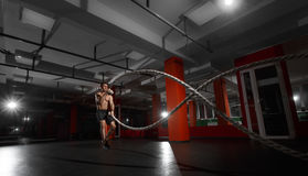Fitness man working out with battle ropes at a gym Royalty Free Stock Photography
