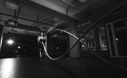 Fitness man working out with battle ropes at a gym. Fitness man working out with battle ropes at gym. Battle ropes fitness man at gym workout exercise fitted Stock Images