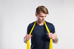 Fitness man working out with resistance bands, studio shot. Stock Image