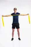 Fitness man working out with resistance bands, studio shot. Handsome hipster fitness man in dark blue t-shirt and black shorts working out with resistance bands Stock Photography