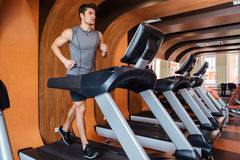 Fitness man working out and running on treadmill in gym Stock Image