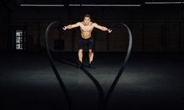 Fitness man workout with battle ropes at gym. training exercise fitted body in club. Torso. Fitness man workout with battle ropes at gym. training exercise Royalty Free Stock Photography